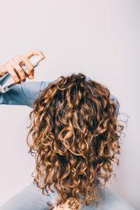 Woman using shine spray for hair